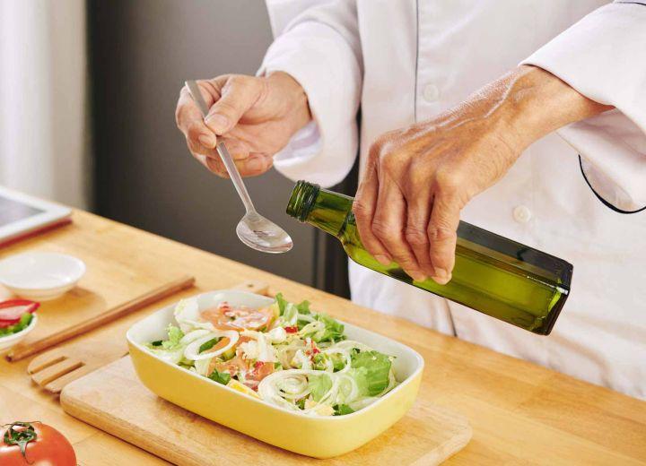 chef cocinando y vertiendo aceite de oliva virgen en cuchara